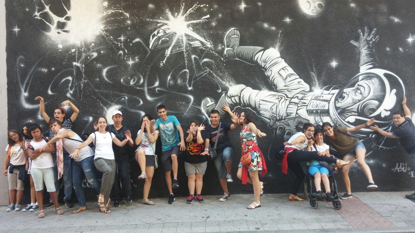 Integrantes de AVIVA posan junto a una de las obras de la Galería Urbana.